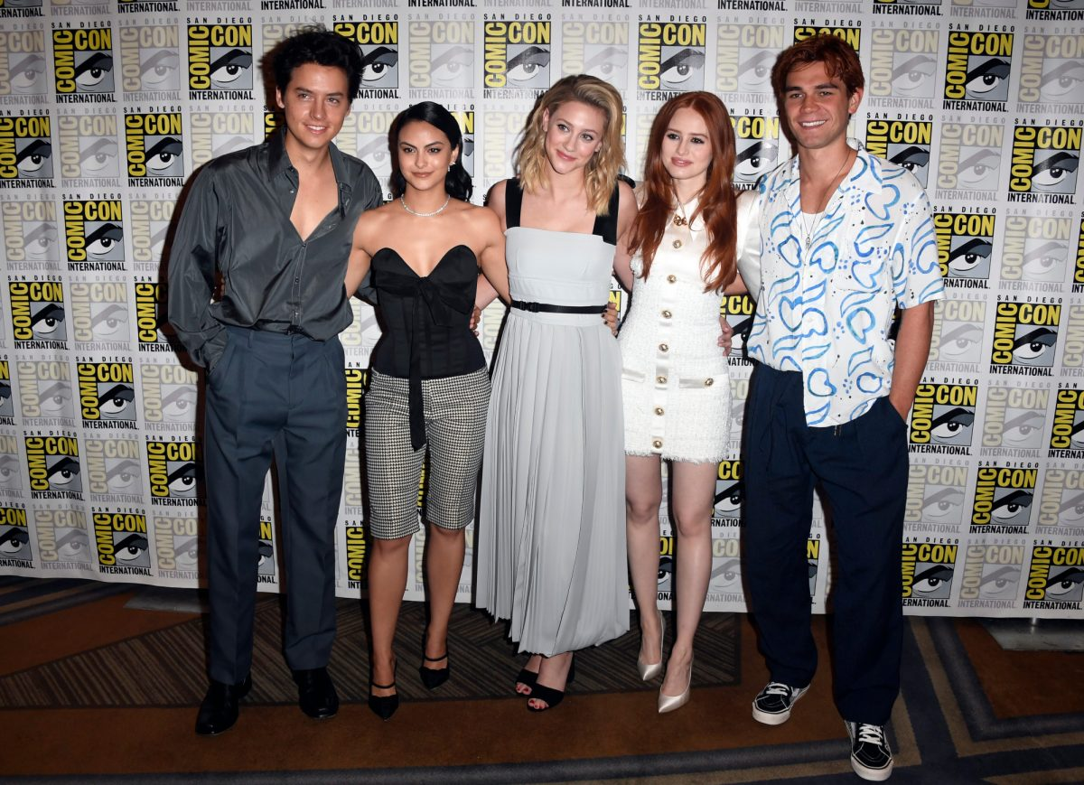 'Riverdale' Season 5 stars Cole Sprouse, Camila Mendes, Lili Reinhart, Madelaine Petsch, and K.J. Apa. They're standing side by side in front of a Comic-Con wall and wearing clothes that mix casual and formal styles.