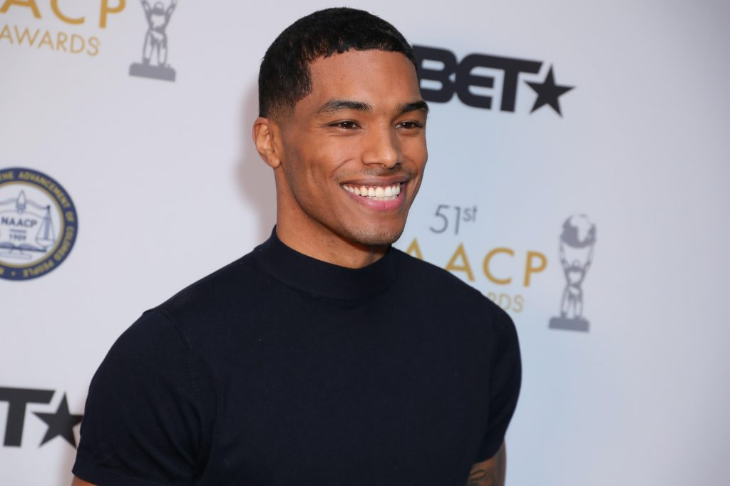 Rome Flynn smiling in front of a white background