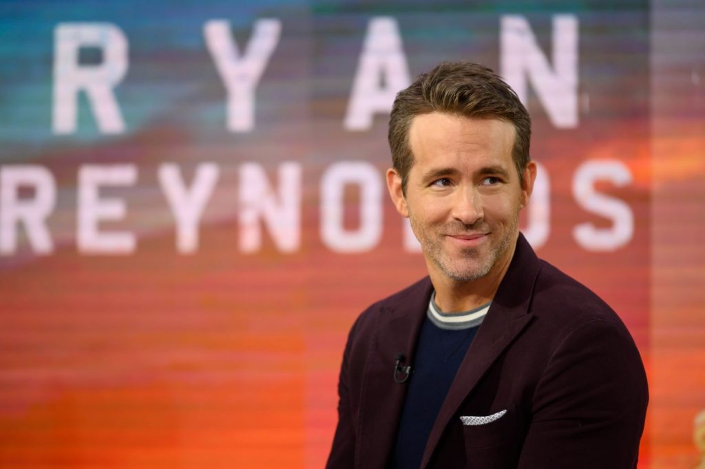 Ryan Reynolds dressed in a black t-shirt with a maroon color jacket standing in front of a red and blue background with his name written in white behind him.