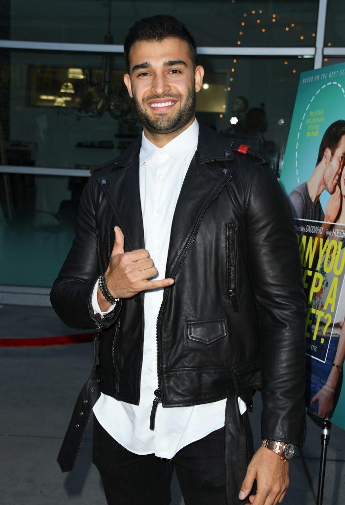 Sam Asghari flashes the hang loose sign with one hand while wearing a black leather jacket and smiling.