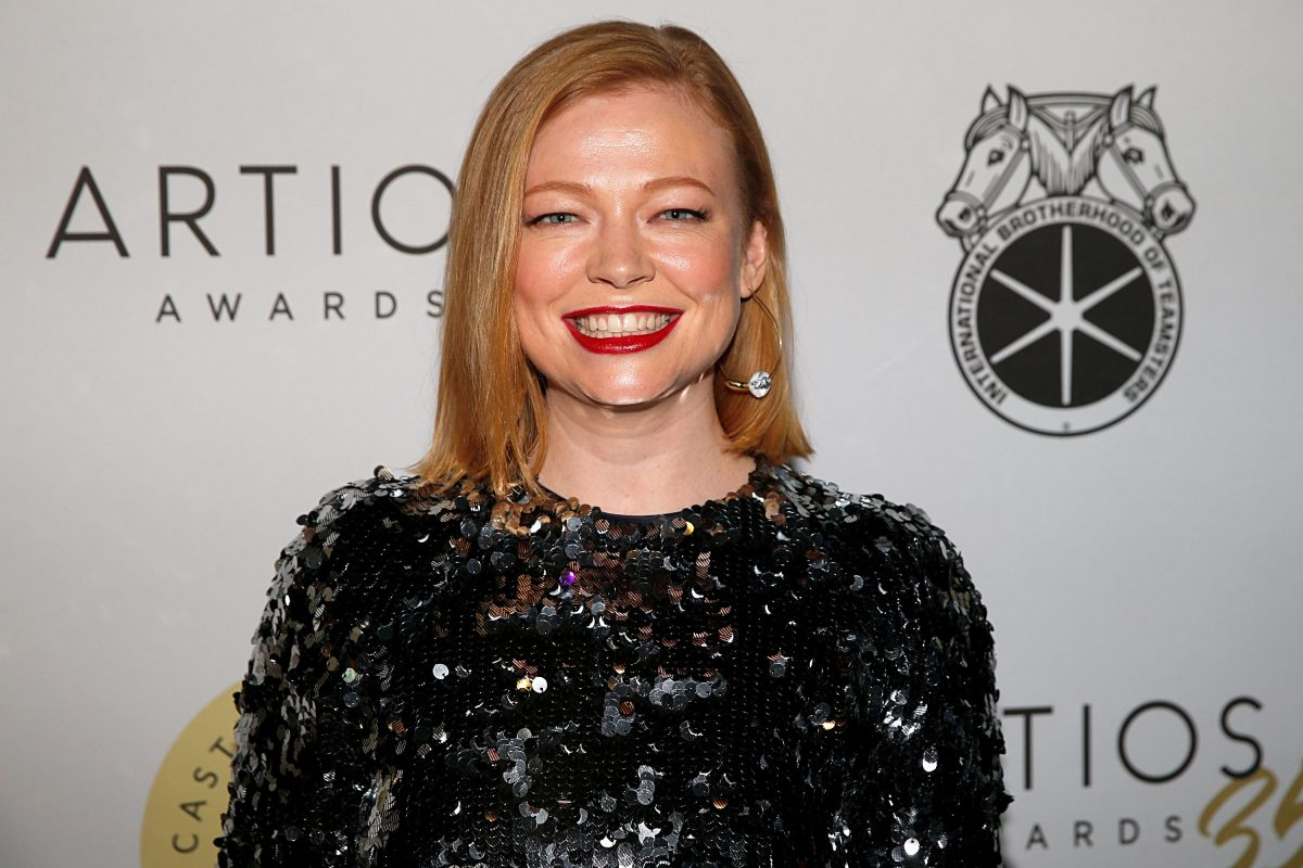 Sarah Snook smiling in a black shimmery dress from chest up.