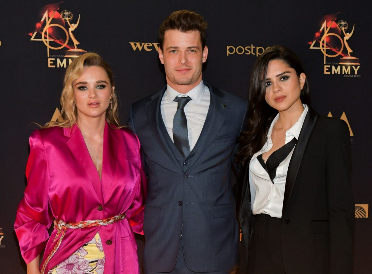 Actors Hunter King, Michael Mealor, and Sasha Calle huddle together and pose for a picture on the red carpet. Hunter wears a pink suit jacket, Michael wears a dark suit and tie, and Sasha wears a black suit over a white button up shirt.