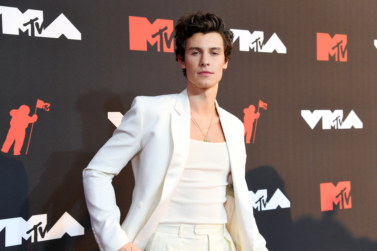 Shawn Mendes wearing a white suit jacket over a white tank top and pants, posing at an event.