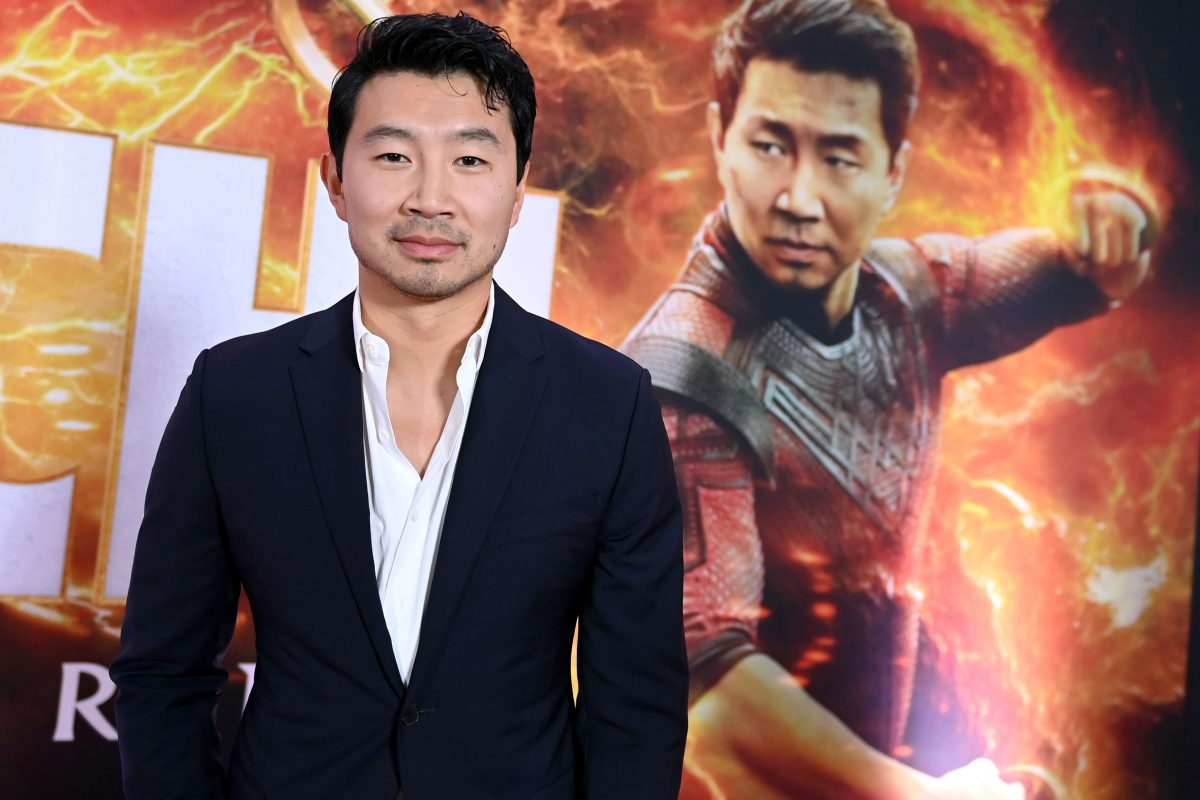 Actor Simu Liu standing in a white shirt and black jacket from waist up in front of his poster from the Marvel movie 'Shang-Chi and the Legend of the Ten Rings.'