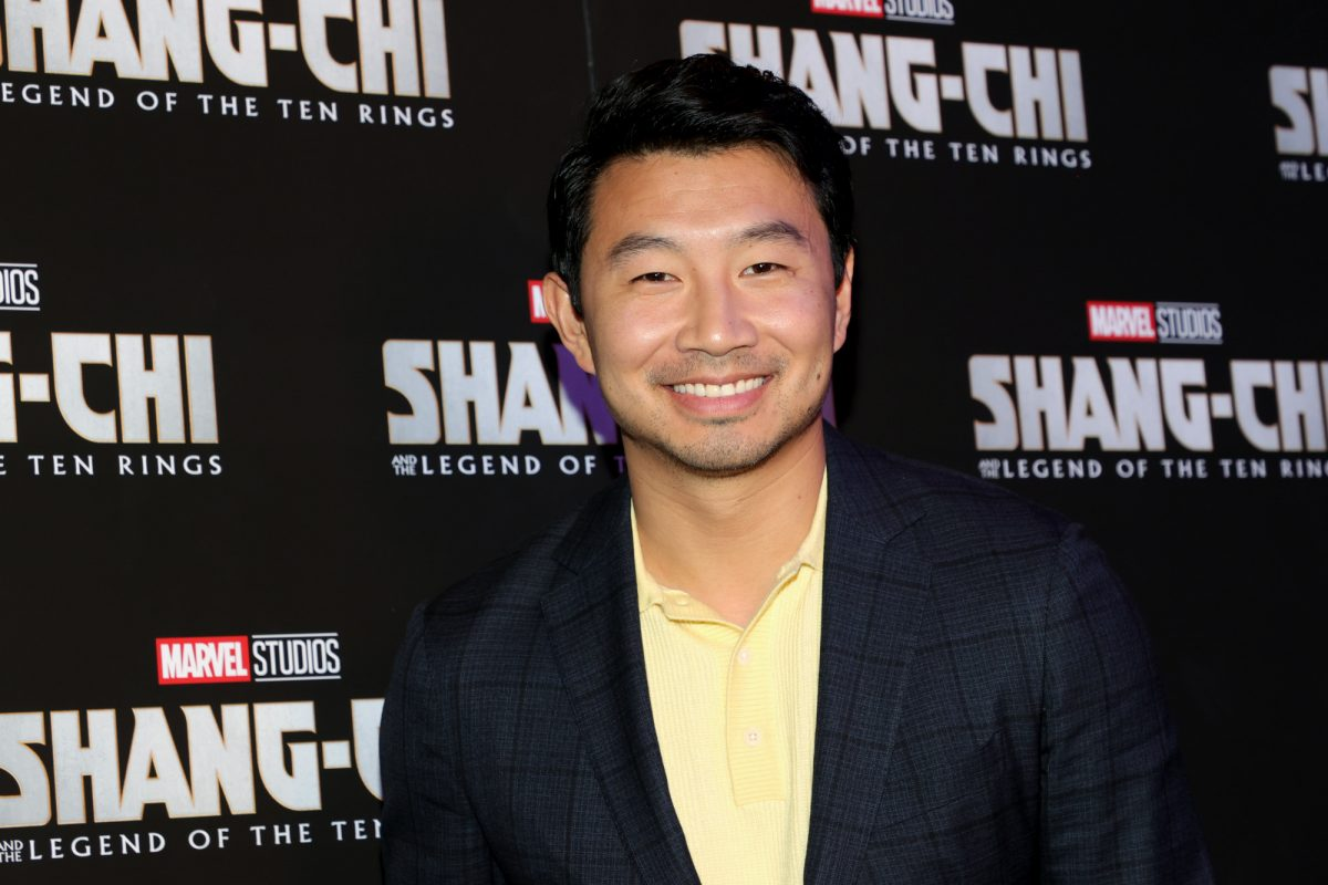 'Shang-Chi and the Legend of the Ten Rings' star Simu Liu. He's wearing a yellow button-up shirt and black jacket. He's smiling at the camera and standing in front of a wall with the 'Shang-Chi' logo all over it.
