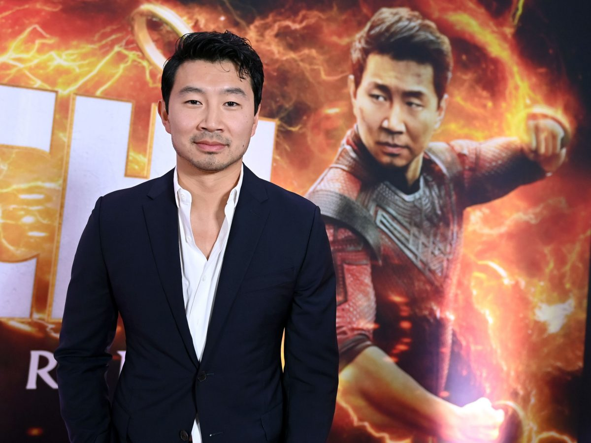 Marvel star Simu Liu at the premiere for 'Shang-Chi and the Legend of the Ten Rings.' He's wearing a white button-up shirt and black jacket. He's staring at the camera and standing in front of an image of his character, Shang-Chi.