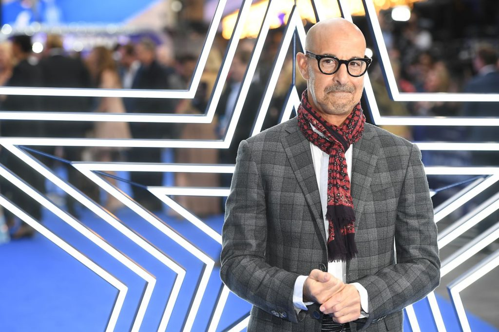 Stanley Tucci dressed in a black and grey plaid suit standing in front of a metal star with multiple layers of the shape from big to small.