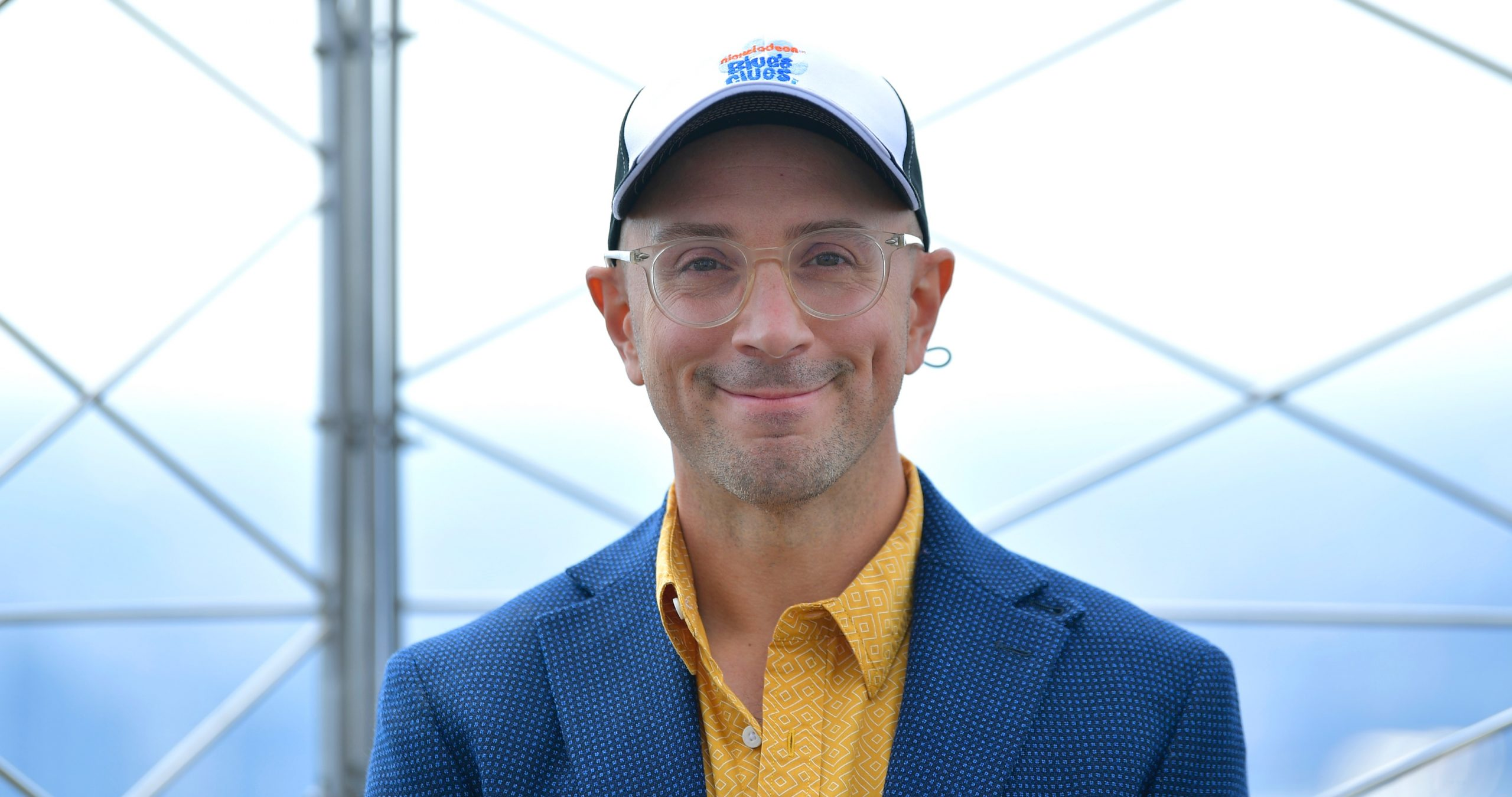 'Blue's Clues' host Steve Burns at 25th Anniversary celebration in a blue suit jacket and yellow button up.