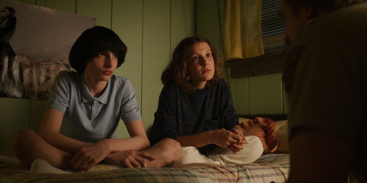Mike Wheeler, played by Finn Wolfhard, sitting on a bed with Eleven, played by Millie Bobby Brown, in a production still from 'Stranger Things' Season 3.
