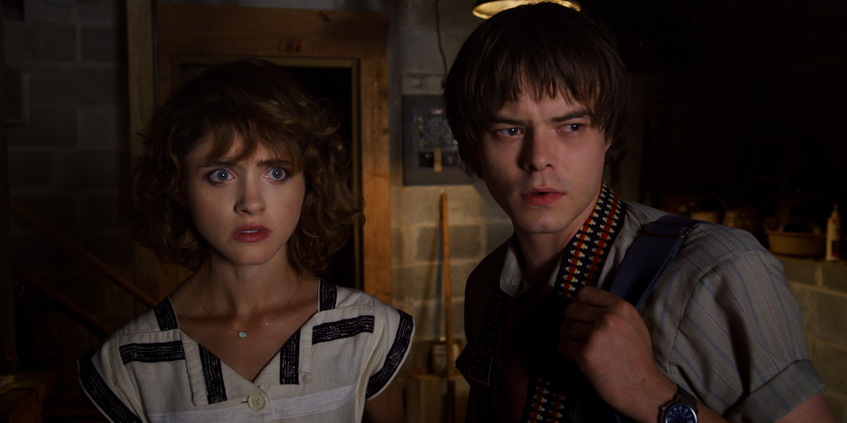 Natalia Dyer and Charlie Heaton look on as Nancy Wheeler and Jonathan Byers in a 'Stranger Things' Season 3 production still.