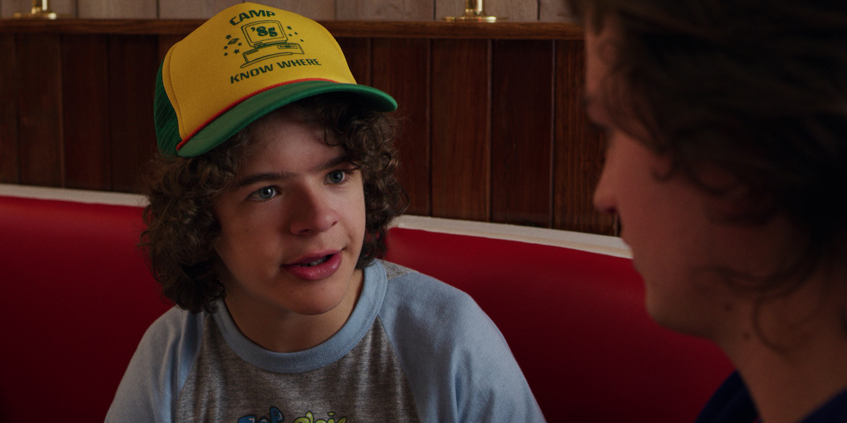 Gaten Matarazzo as Dustin looks at the camera in a yellow and green hat in a production still from 'Stranger Things' Season 3.