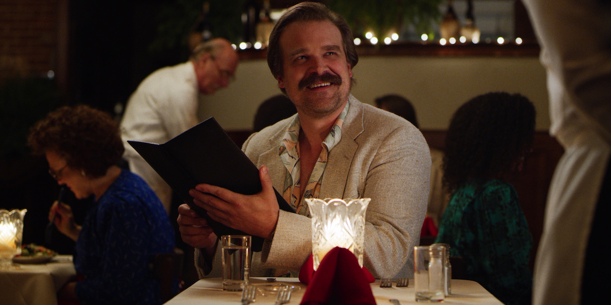 David Harbour as Chief Jim Harbour holding a menu at a restaurant in a production still from 'Stranger Things' Season 3.