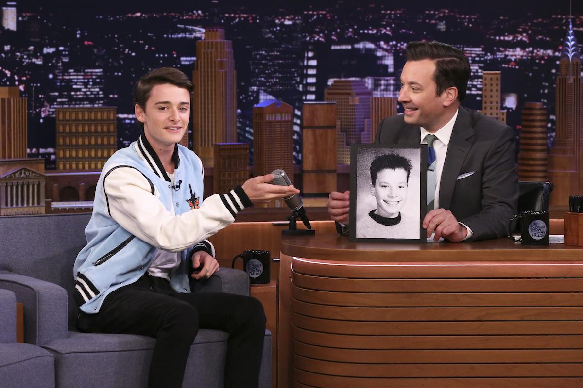 Noah Schnapp from 'Stranger Things' Season 4 in a light blue jacket talking to Jimmy Fallon on 'The Tonight Show.'