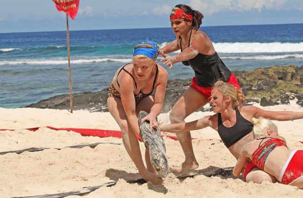 Jessica 'Sugar' Kiper, Sandra Diaz, Candice Woodcock, and Courtney Yates from the 'Survivor' cast trying to grab a log on the beach for a reward challenge. Kiper recently spoke out about 'Survivor' Season 41