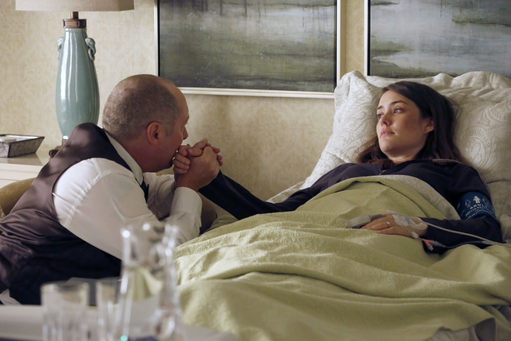 James Spader as Raymond 'Red' Reddington sits next to Megan Boone as Elizabeth Keen as she lays in a hospital bed. He's kissing her hand.
