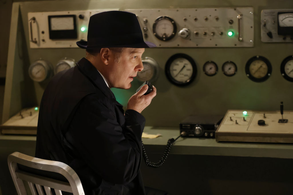 James Spader as Raymond 'Red' Reddington speaks into a transponder from the Latvia sit. He's wearing a dark suit and fedora.