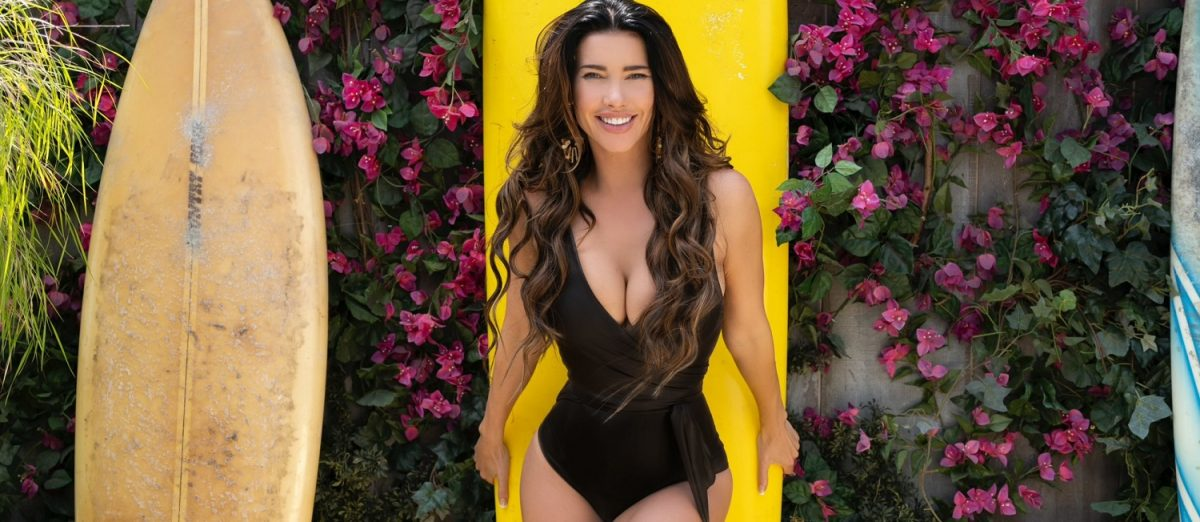 The Bold and the Beautiful sneak peek focuses on Steffy, pictured here in a brown one-piece swimsuit leaning against a yellow surfboard