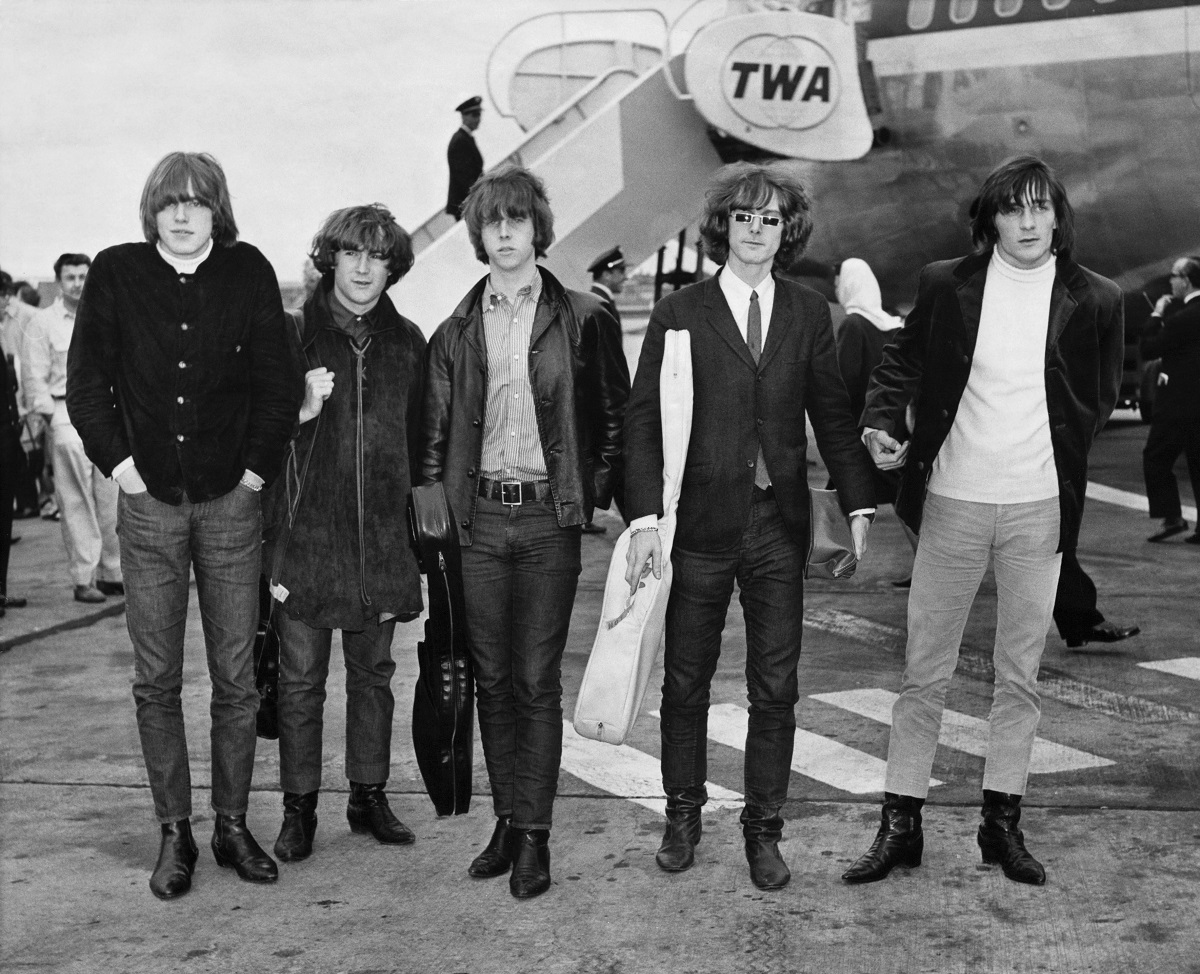 The Byrds on an airport tarmac in front of a plane in a black and white image.