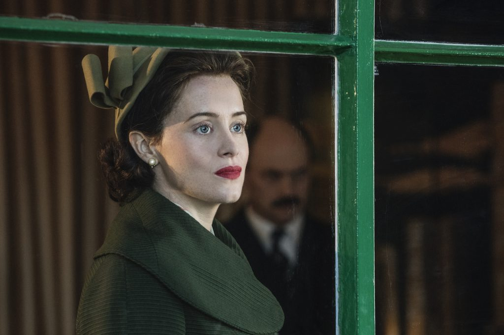 Claire Foy as Queen Elizabeth II on 'The Crown' wears a green dress and hat. She looks out a window.