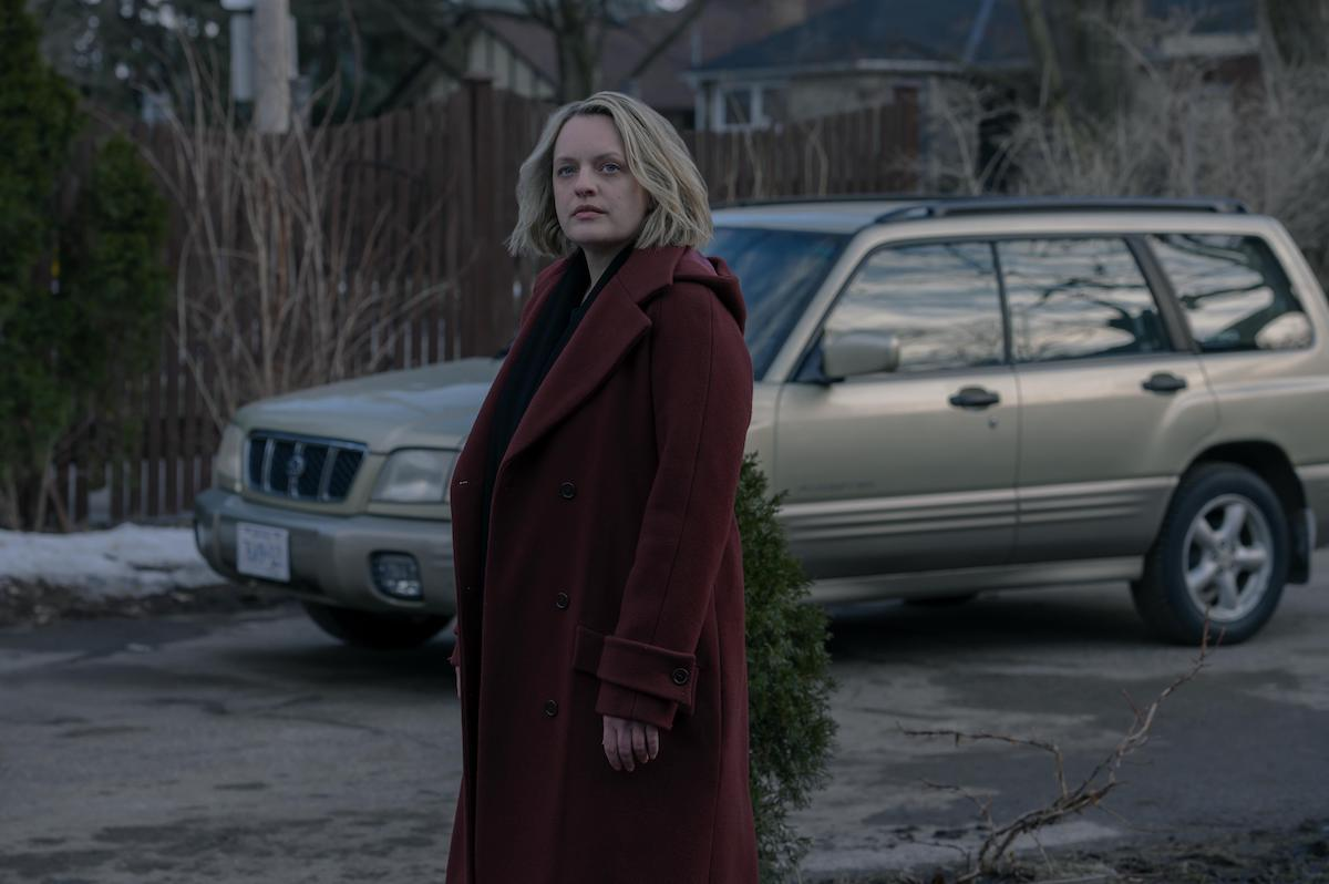 Elisabeth Moss as June in 'The Handmaid's Tale' Season 4 Episode 10, 'The Wilderness.' She stands in a driveway looking at a house that's offscreen. Moss is wearing a long red coat that's similar in color to the dress she had to wear as a Handmaid in Gilead. It's daytime in the winter.