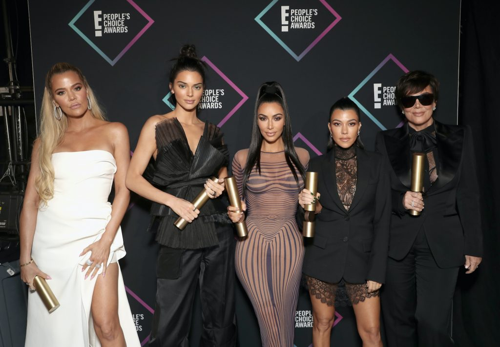 The Kardashian family in front of a black background