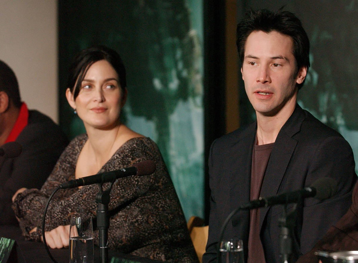Carrie-Anne Moss looks at Keanu Reeves as he speaks into a microphone.