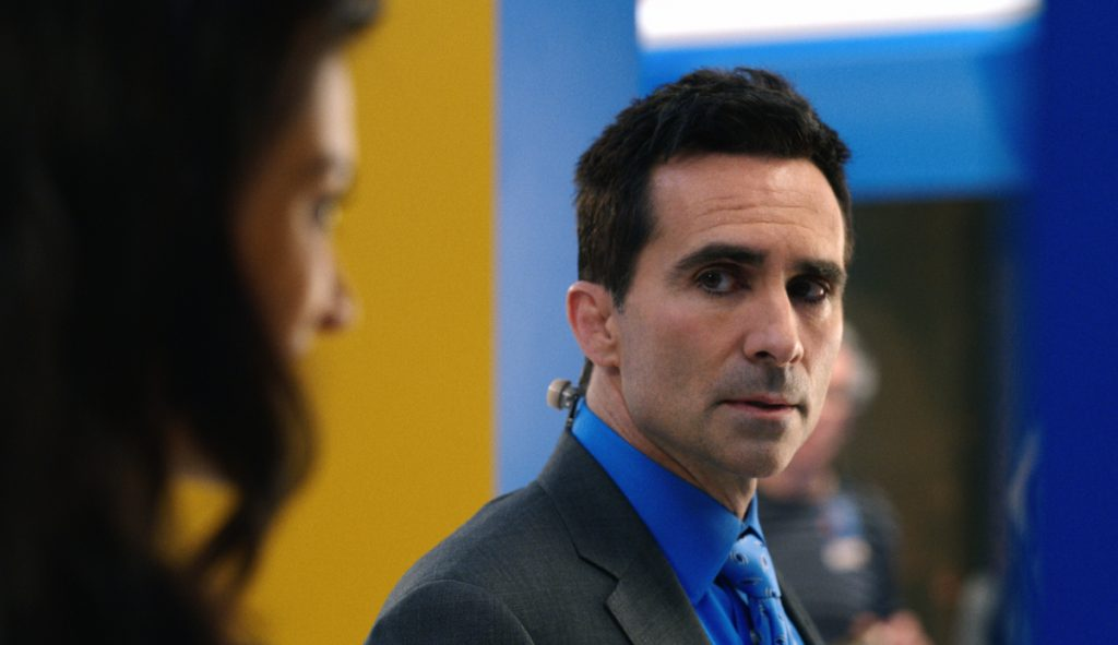 Yanko looks to the side at a woman. He is wearing a black suit jacket with a blue shirt and tie.