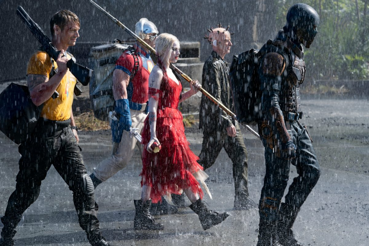 Joel Kinnaman as Rick Flag, John Cena as Peacemaker, Margot Robbie as Harley Quinn, Peter Capaldi as The Thinker and Idris Elba as Bloodsport in 'The Suicide Squad.' The group walks together in the rain, headed somewhere to the right of screen. Bloodsport leads them wearing all black and a black helmet, and Harley Quinn wears a ruffled red dress and combat boots. The film is streaming on HBO Max and available in theaters.
