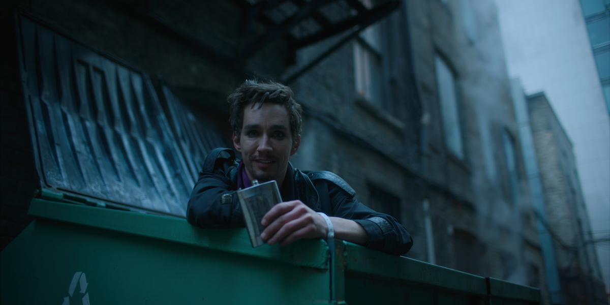 Robert Sheehan as Klaus Hargreeves leaning over the edge of a dumpster with a flask in his hand in a scene from 'The Umbrella Academy' Season 1.