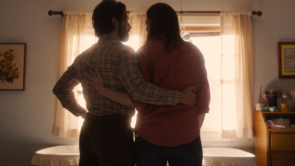 Milo Ventimiglia as Jack Pearson, Mandy Moore as Rebecca Pearson stand side-by-side with their back to the camera with their arms across each other's backs.