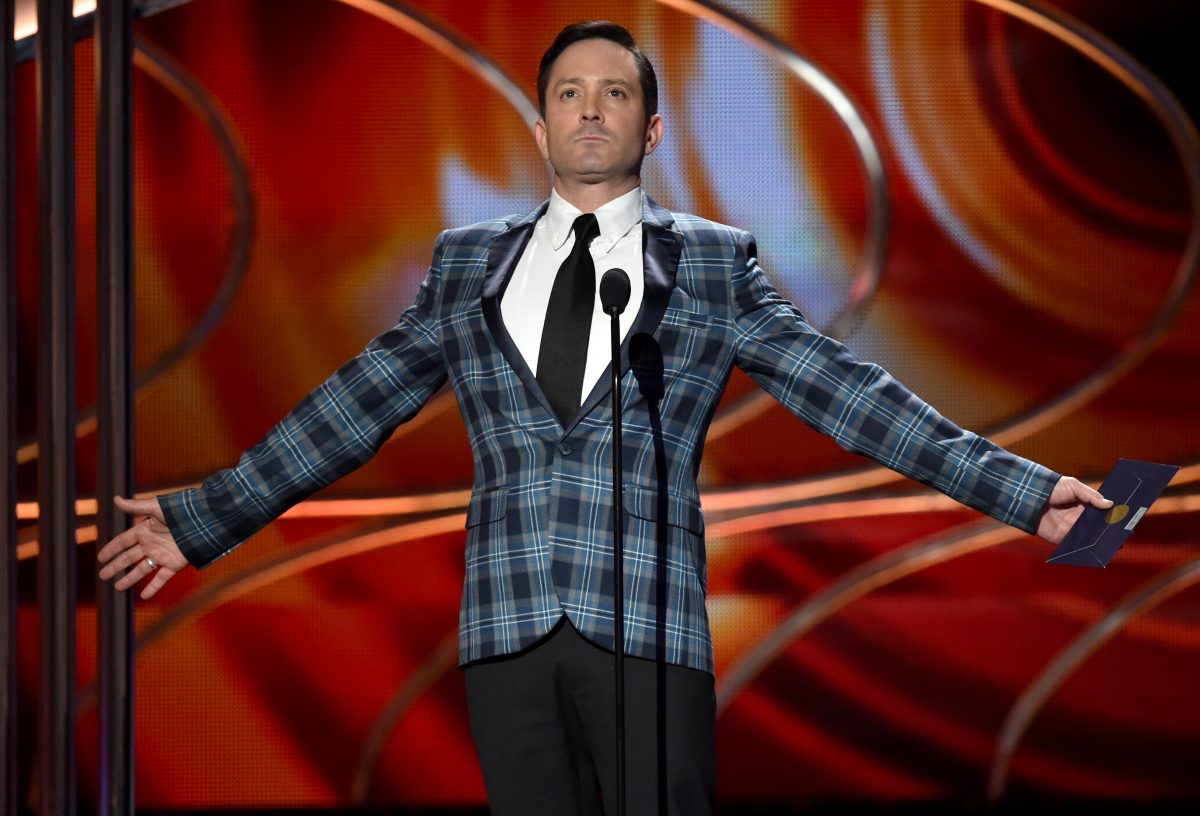'Supergirl' actor Thomas Lennon wears a blue plaid suit onstage of an awards show.