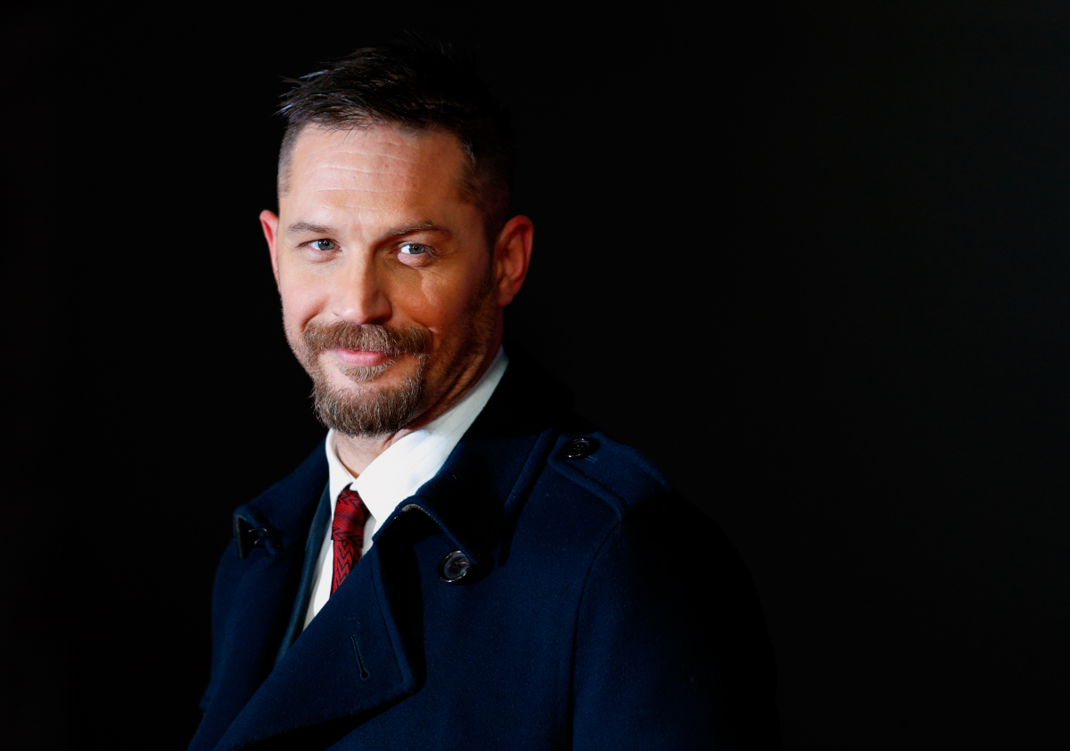 Tom Hardy with a beard and mustache smiling and wearing a blue suit and red tie.