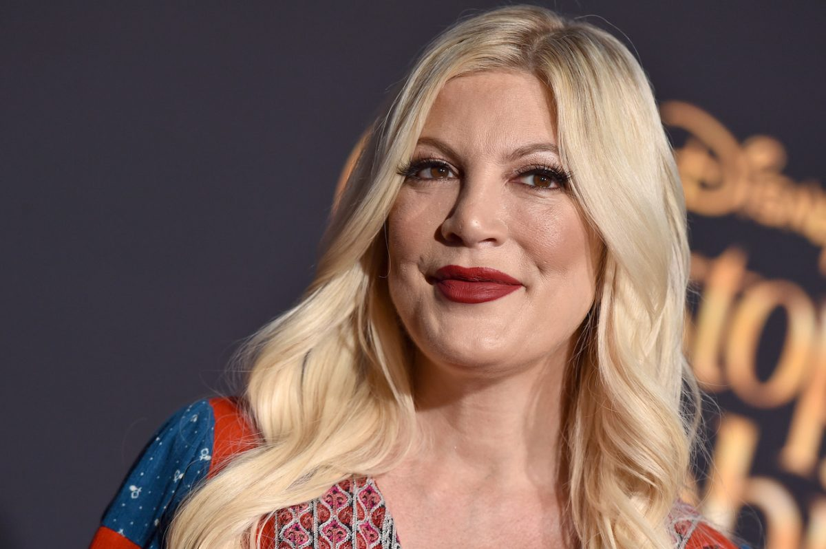 Tori Spelling in front of a gray background