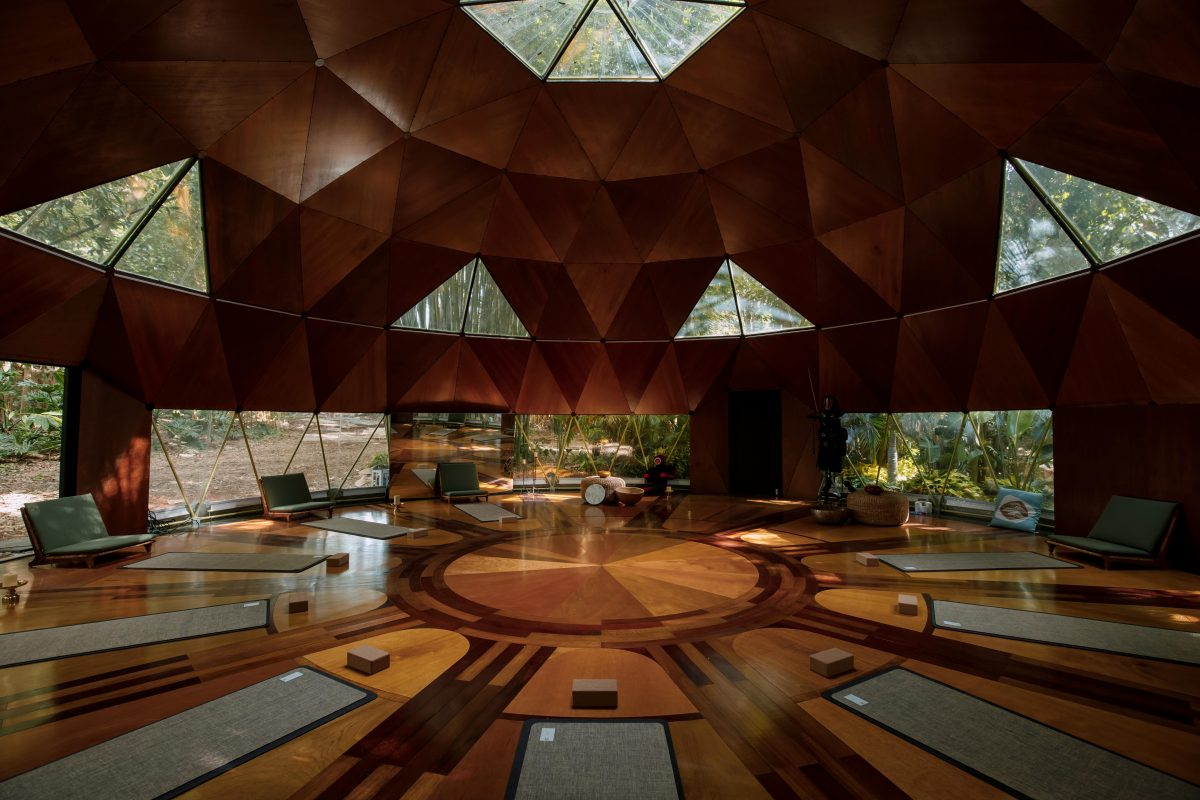 A large yoga/meditation room with big glass windows at Tranquillum House. Nine mats are placed on the floor awaiting guests.