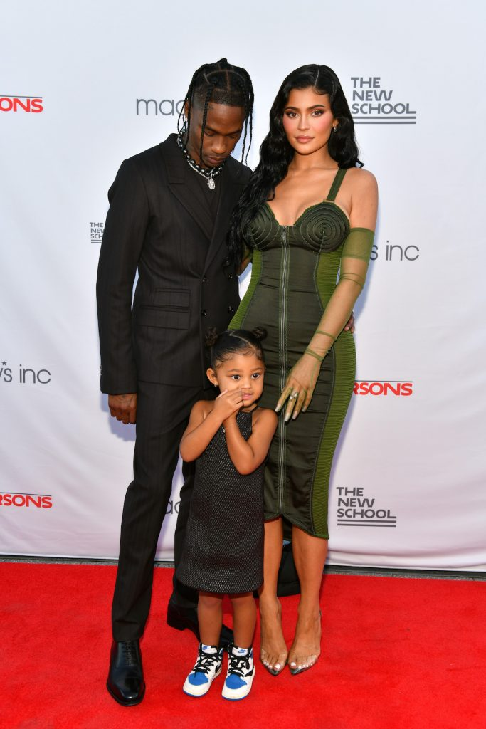 Travis Scott, Kylie Jenner, and their daughter Stormi Webster pose together at an event.