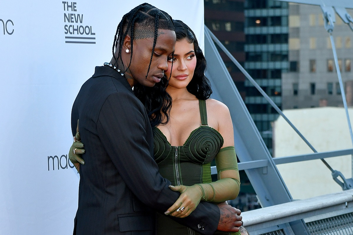 Travis Scott in a black suit and Kylie Jenner in a green dress.