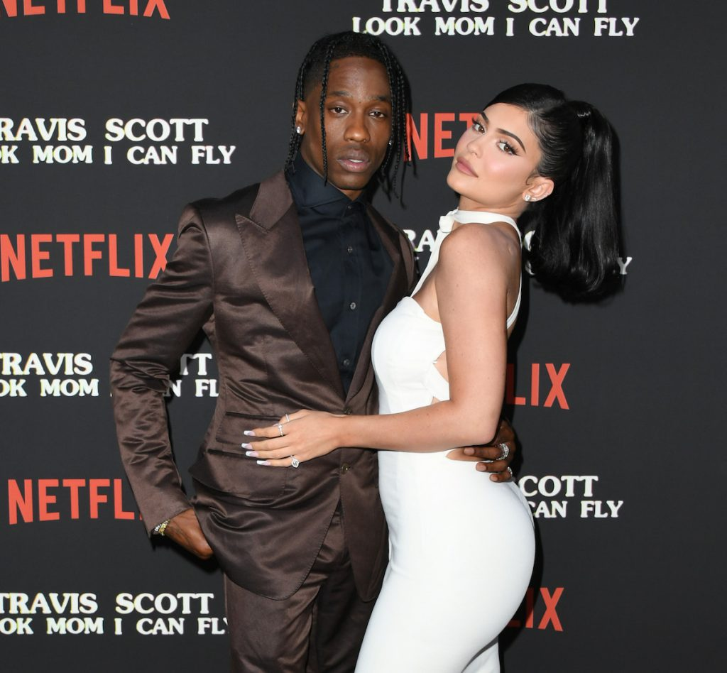 Travis Scott and Kylie Jenner pose together at an event.