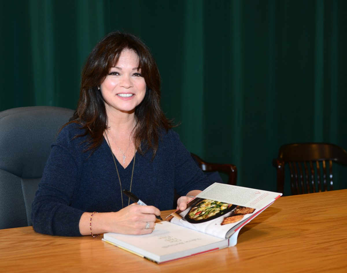 Food Network star Valerie Bertinelli smiles as she signs a copy of her cookbook