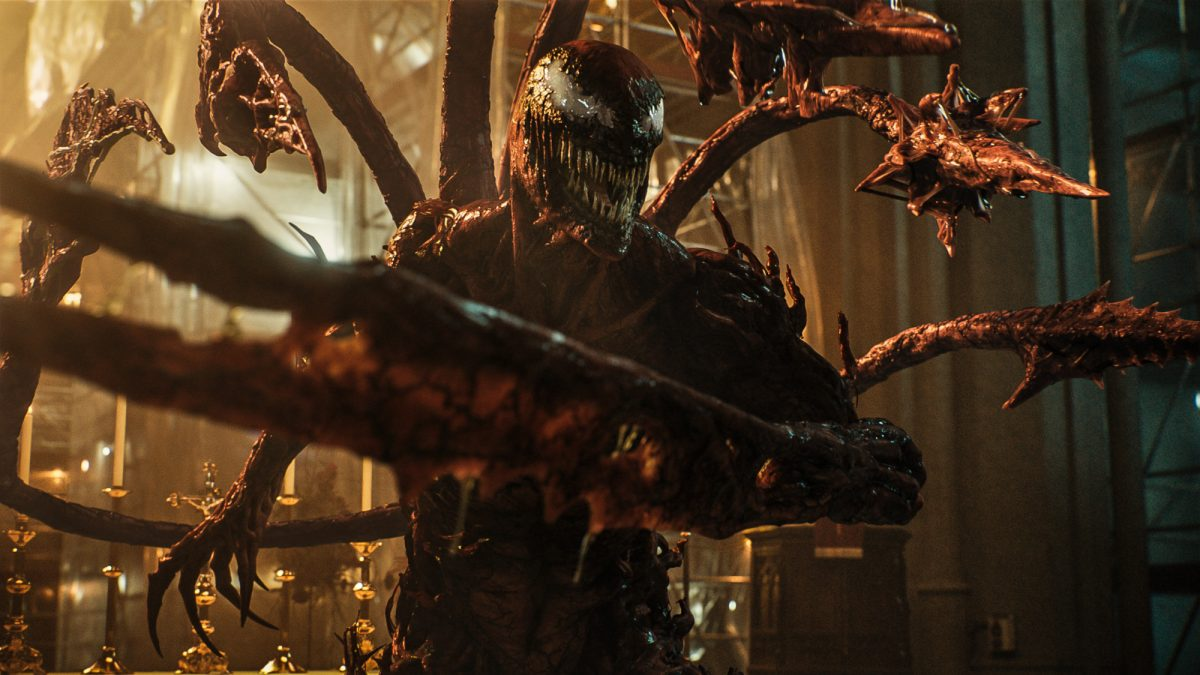 Carnage in Sony Pictures' 'Venom: Let There Be Carnage,' which has a PG-13 rating. His teeth are bared and his spiked limbs are pointing at someone off-screen.
