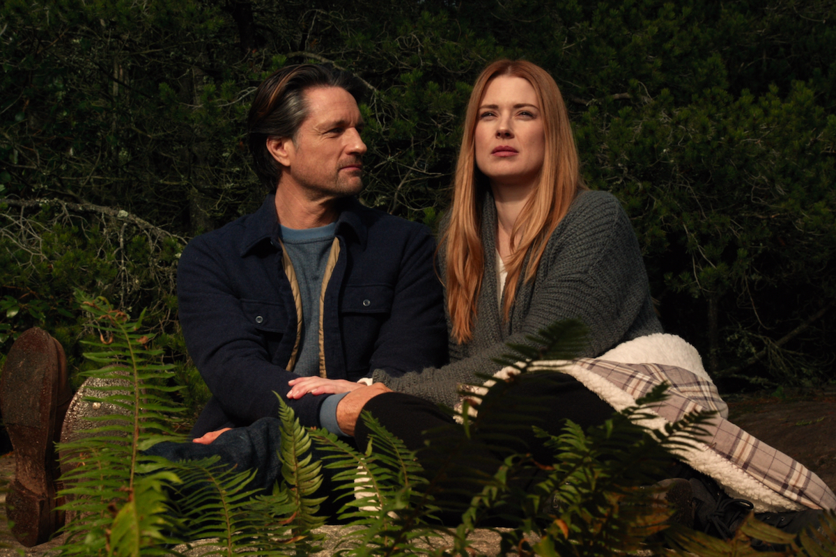 Martin Henderson as Jack Sheridan and Alexandra Breckenridge as Mel Monroe sitting together looking at the stars in 'Virgin River'