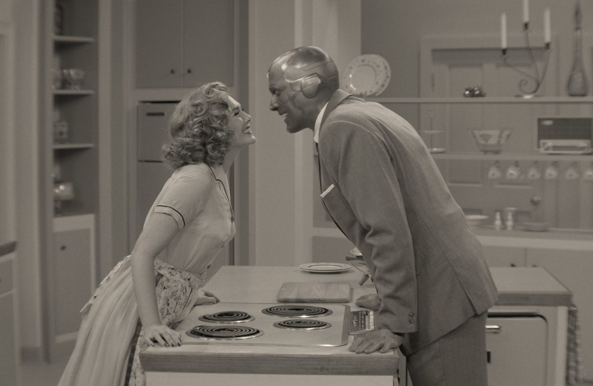 A black-and-white image of the 'WandaVision' premiere. Elizabeth Olsen's Wanda and Paul Bettany's Vision are leaning over a counter and look like they're about to kiss. Will 'WandaVision' take home any Emmys?