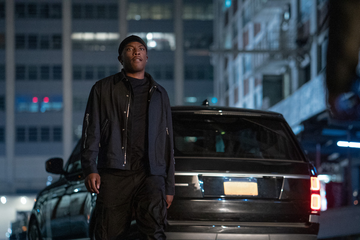 Woody McClain as Cane Tejada dressed in all black standing in front of a car in 'Power Book II: Ghost'