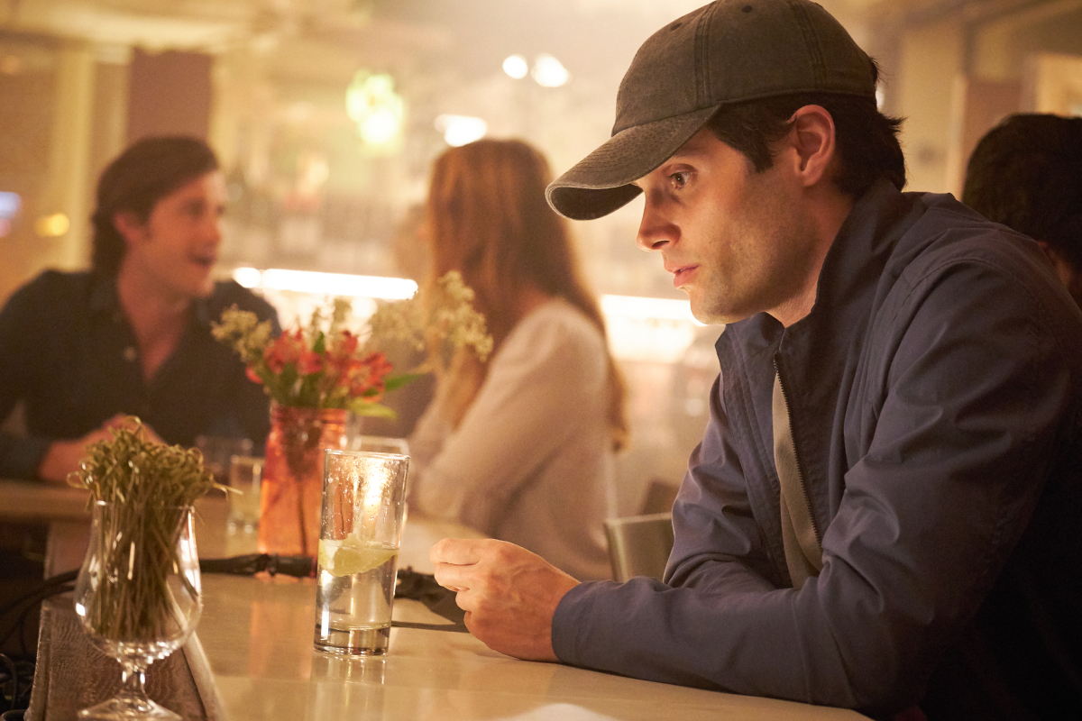 Joe Goldberg sitting at a bar wearing a hat for a disguise.
