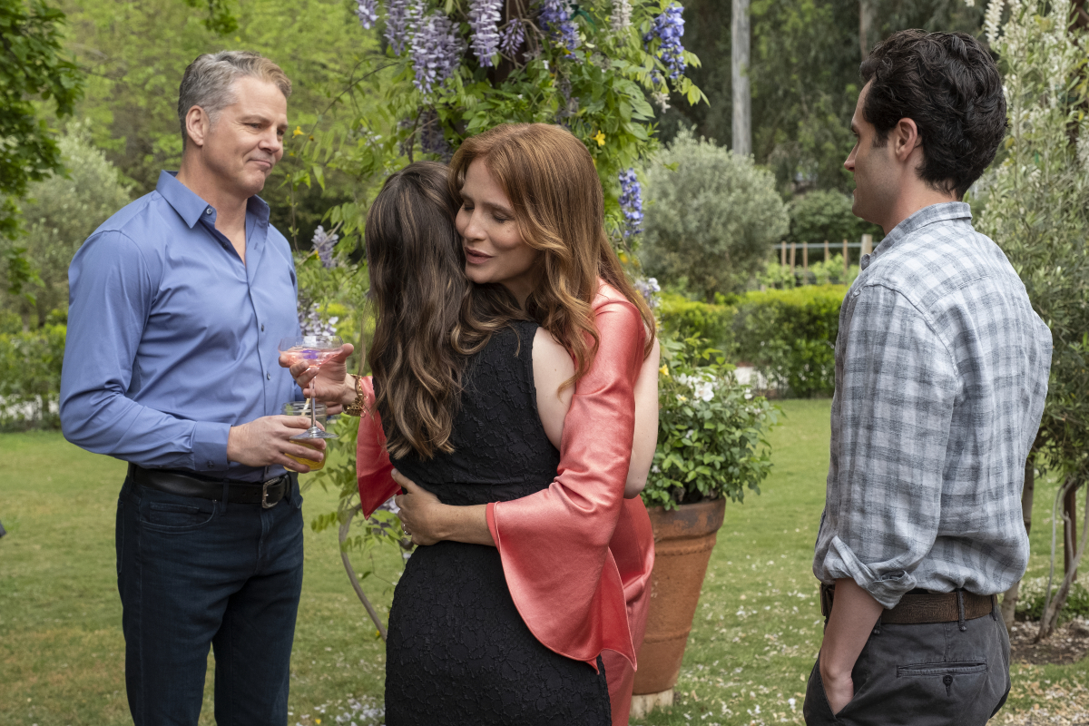 Love Quinn and her mother hug while Love's father and Joe Goldberg stand next to them.