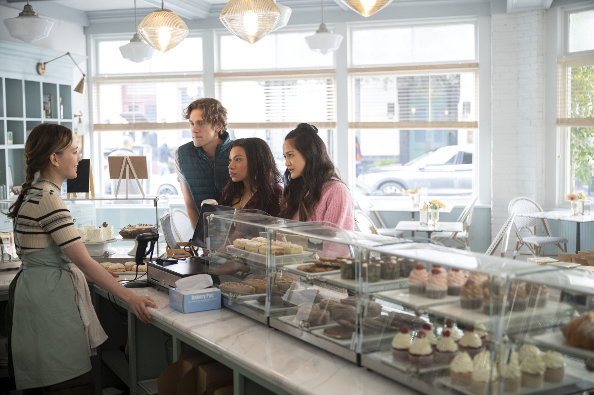 Love stands behind the counter at a bakery and talks to her friends Sherry, Kiki, and Andrew on the other side.