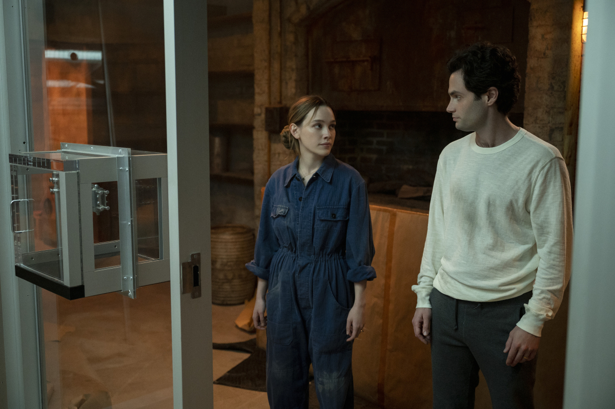 Love Quinn and Joe Goldberg stand outside the glass cage and look at each other in season 3 of 'You.'