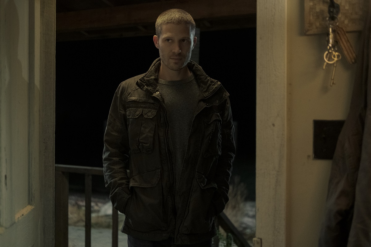 Zach Gilford stands in an open doorway in 'Midnight Mass.'