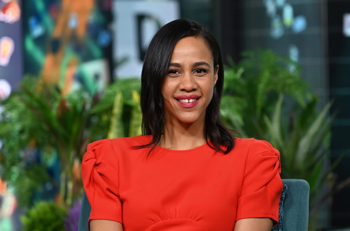Zawe Ashton smiles while wearing a red dress during an appearance on the Build SeriesA=