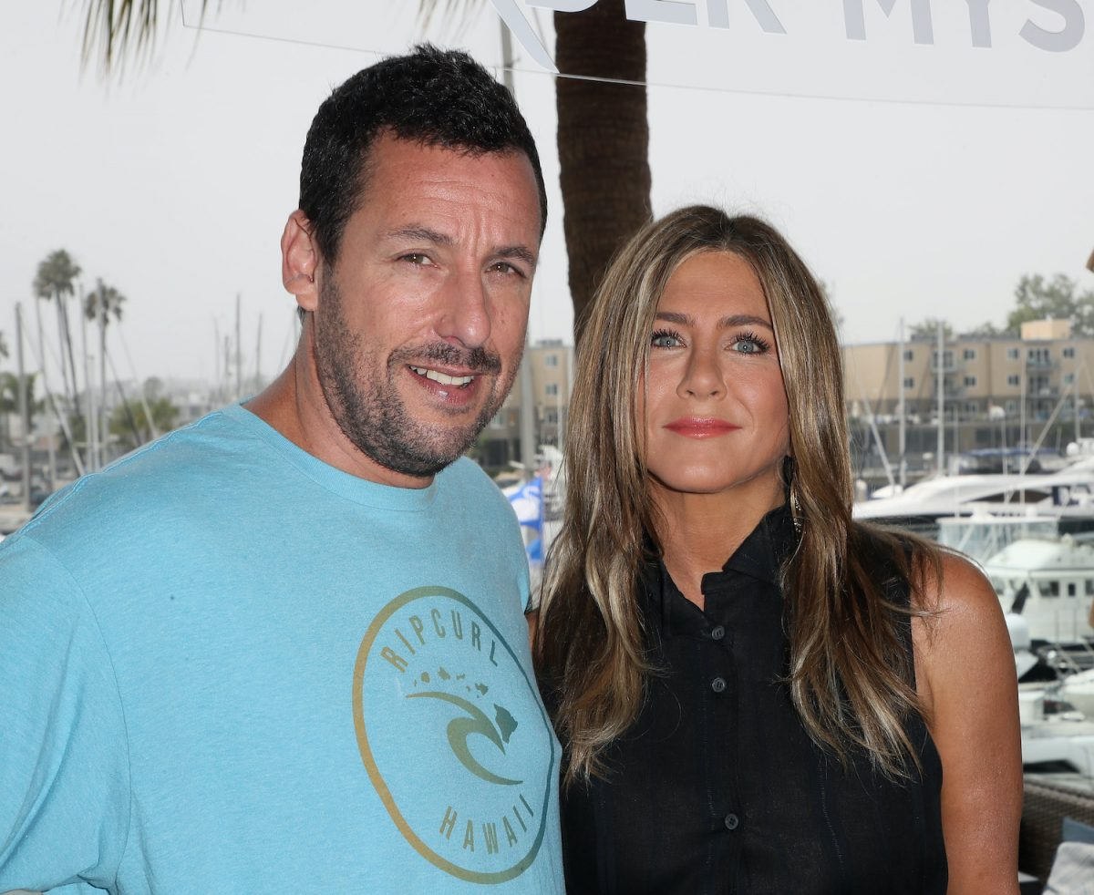Adam Sandler wears a blue shirt and Jennifer Aniston wears a black shirt as they smile during a photocall of Netflix's 'Murder Mystery' in 2019