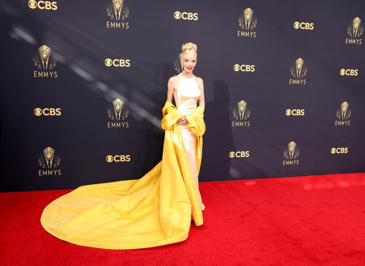 Anya Taylor-Joy wears a pale yellow Dior gown and vibrant yellow opera coat on the 2021 Emmys red carpet